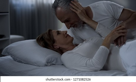 Elderly couple caressing in bed, man kissing woman hand, love in marriage