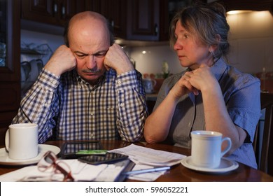 The elderly couple considers their family budget. Problems with money. They are trying to find a solution.