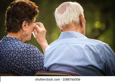 Elderly couple crying and watching sad or happy situation together.