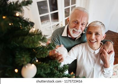 Elderly couple decorating a Christmas tree