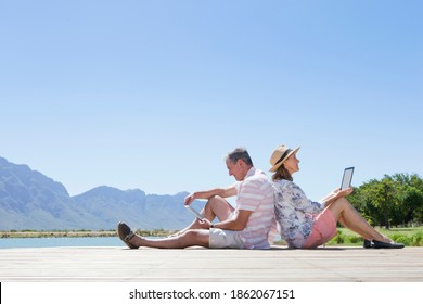 Elderly couple with digital tablets sitting against their backs on a jetty by the lake.