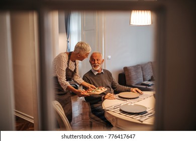 Elderly couple in the dining room. Woman holding a board with food.