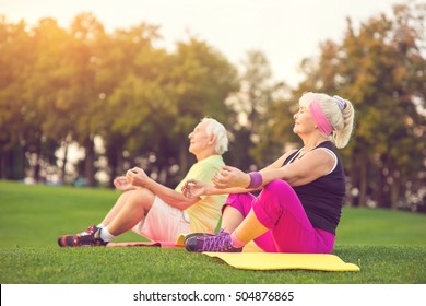 Elderly couple doing yoga. People sitting outdoor. Health of body and mind. Find balance inside yourself.
