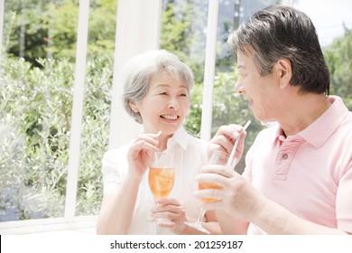 An elderly couple drinking iced tea