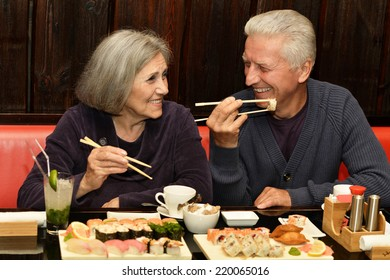 Elderly couple eating sushi in a cafe