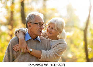 Elderly couple embracing in autumn park