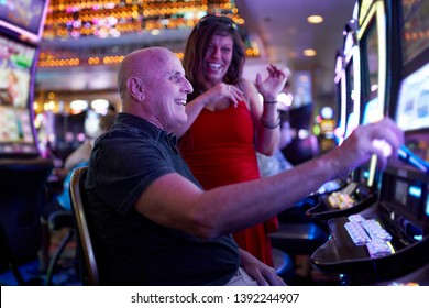 elderly couple gambling on slot machine in casino