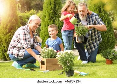 Elderly couple with grandchildren working in garden