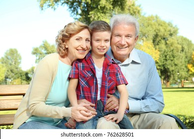 Elderly couple with grandson sitting on bench in park