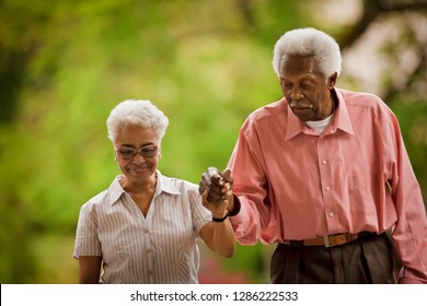 Elderly couple hand in hand together.