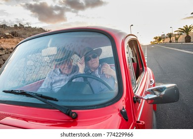 Elderly couple with hat, with glasses, with gray and white hair, with casual shirt, on vintage red car on vacation enjoying time and life. With a cheerful mobile phone smiling