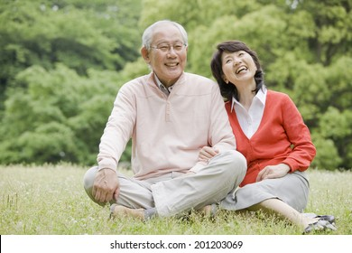 The elderly couple having a conversation upon sitting on the grass of the park