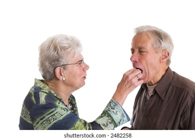 Elderly couple having fun; the woman is putting a chocolate in her husbands mouth
