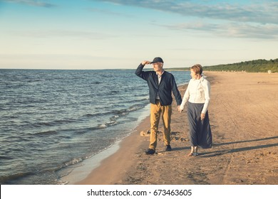 elderly couple having romantic walk on the beach at sunset