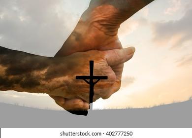 Elderly couple holding hands against cross religion symbol shape over sunset sky