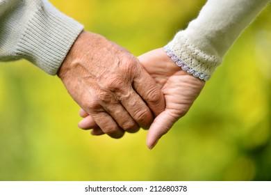 Elderly couple holding hands over natural background