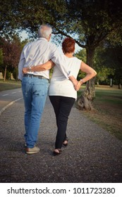 ELDERLY COUPLE HOLDING HANDS WALKING DOWN IN A PARK