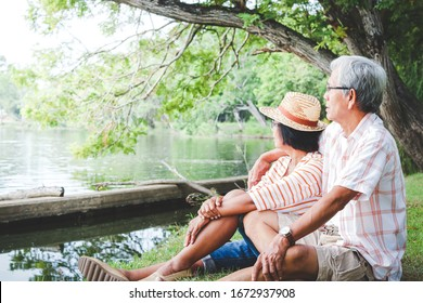 An elderly couple hugging each other with love and happiness in a park with a large pond. Senior community concept, good health, longevity