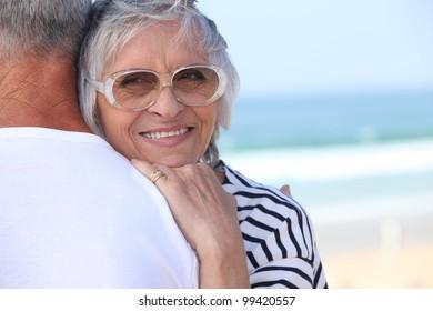 Elderly couple hugging on beach