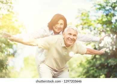 Elderly couple hugging and smiling at camera