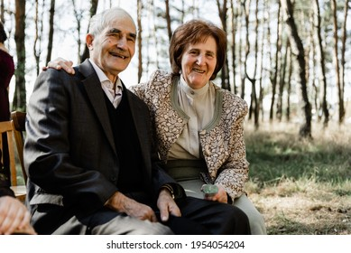 An elderly couple hugs in an autumn park sits on a bench. happy and smiling senor and senorita. pensioners are looking at the camera. grandparents hugging