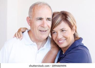 Elderly couple hugs each other tenderly