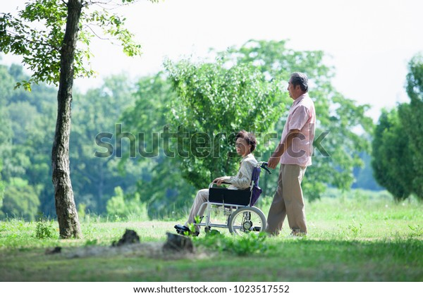 Elderly couple of the Japanese to take a walk in a wheelchair