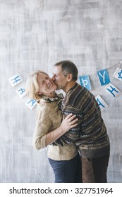 Elderly couple kissing against of the grey wall decorated with Christmas garlands
