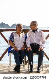 Elderly couple looking at each other laughing. Elderly couple with the sea background.