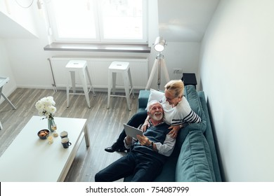 Elderly couple lying on the sofa holding a digital tablet