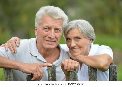 Elderly couple near the fence enjoing nature