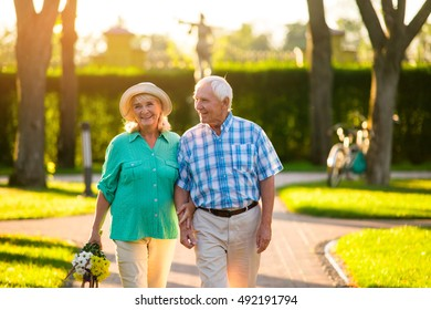 Elderly couple on nature background. Man and woman with bouquet. Love tested by time. Stay devoted and honest.