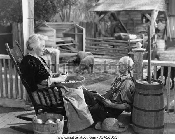 Elderly couple on porch of farmhouse