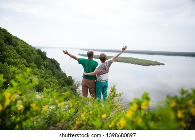 elderly couple on the top of mountain with hands up. Senior couple walking in nature