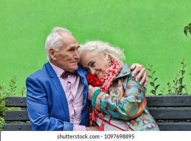 Elderly couple on a walk in the park, sitting on a bench. Rendezvous, love. bright make-up, stylish fashionable clothes. Hipsters. concept love