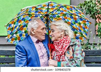 Elderly couple on a walk in the park, siting under an umbrella. Rendezvous, love. bright make-up, stylish fashionable clothes. Hipsters. concept love