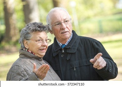 Elderly couple outdoors, pointing