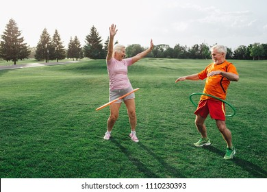 elderly couple in park practising with hula hoops, have fun and enjoy the rest
