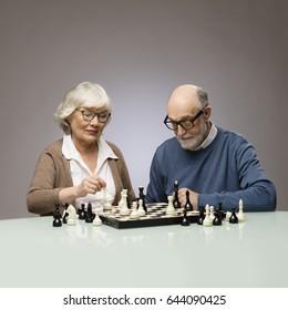 Elderly couple playing chess, studio shot on gray background