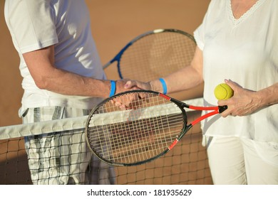Elderly couple playing tennis on the court