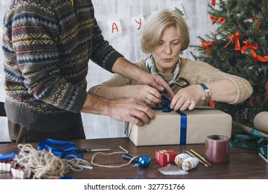 Elderly couple preparing for Christmas and decorating the Christmas present box