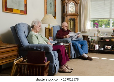 An elderly couple quietly enjoy each others company as they read together in their comfortable living room.
