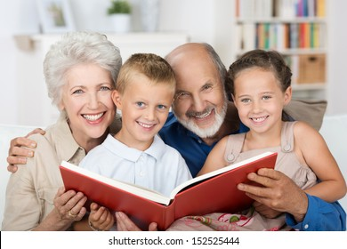 Elderly couple reading to their grandchildren as they all sit close together on a sofa