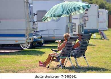 elderly couple is resting on chairs under a beach umbrella near a caravan