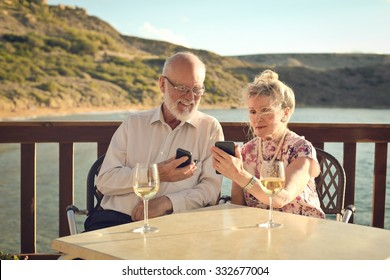 Elderly couple at the seaside using technology
