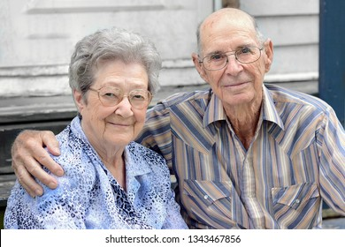 An elderly couple is sitting down on a porch with their arms around each other, smiling and in love. Two caucasian senior citizens are embracing each other on Mothers day in Delcambre, Louisiana.