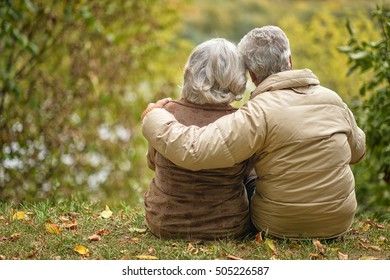 Elderly couple sitting with his back embracing in autumn park