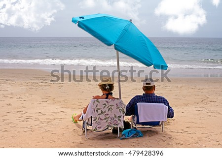 Elderly couple sitting on a beach underneath an umbrella, enjoying their retirement