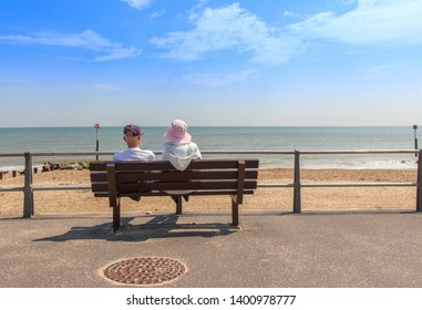 Elderly couple sitting on a bench looking out to sea at Avon Beach, Mudeford, Christchurch, Dorset UK