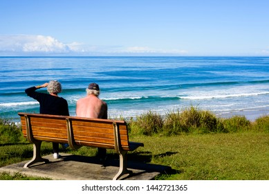 An elderly couple sitting on a bench at a beach in midday sun.